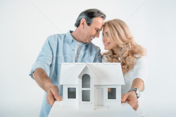 portrait of smiling mature couple showing house model on white Stock photo © LightFieldStudios
