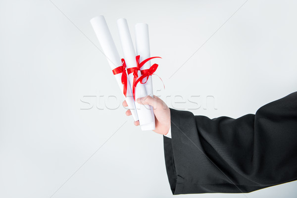 Close-up partial view of student holding diplomas on grey   Stock photo © LightFieldStudios