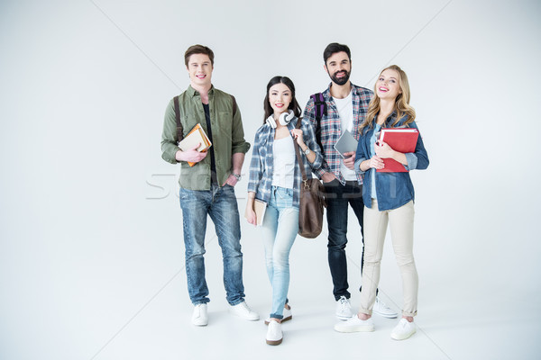 four young students in casual clothes holding books on white Stock photo © LightFieldStudios
