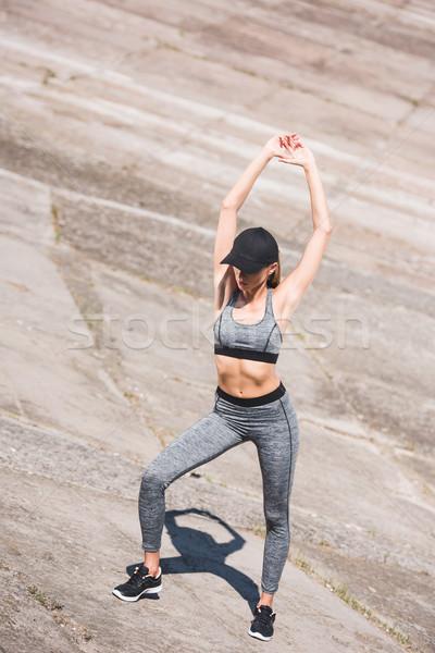 Nő nyújtás sportos sportruha sapka fitnessz Stock fotó © LightFieldStudios