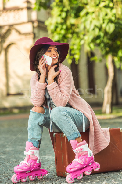 girl in roller skates with smartphone and suitcase Stock photo © LightFieldStudios