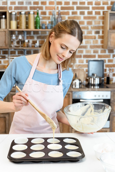 Smiling young woman in apron putting dough in baking form Stock photo © LightFieldStudios
