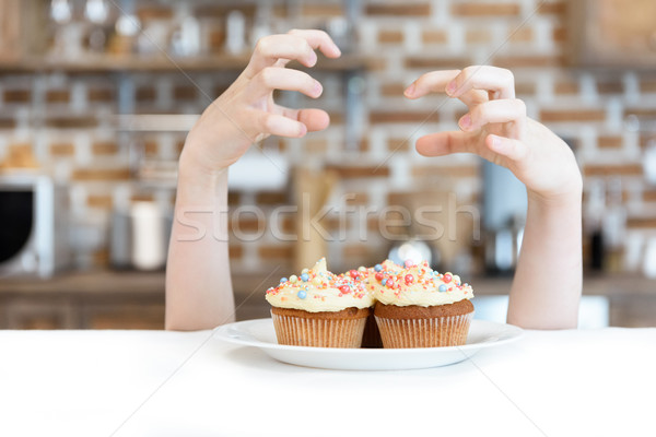 Close-up partial view of little girl and tasty cupcakes on plate Stock photo © LightFieldStudios