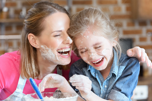 portrait of laughing mother and daughter cooking at home Stock photo © LightFieldStudios