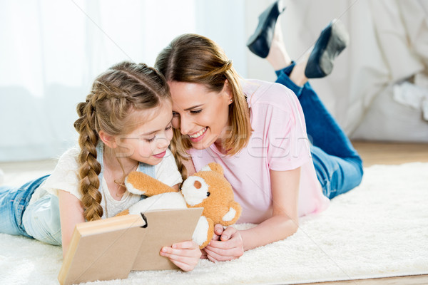 Stock photo: Happy mother and daughter with teddy bear reading book on carpet