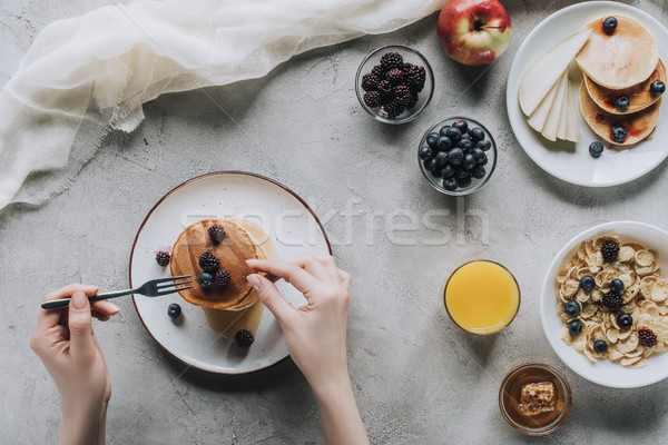 cropped shot of person eating delicious homemade pancakes with berries for breakfast Stock photo © LightFieldStudios