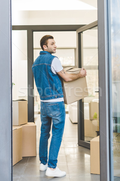 back view of man with cardboard box moving new house Stock photo © LightFieldStudios