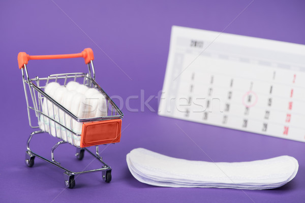 tampons in small shopping cart, daily liners and calendar on purple Stock photo © LightFieldStudios