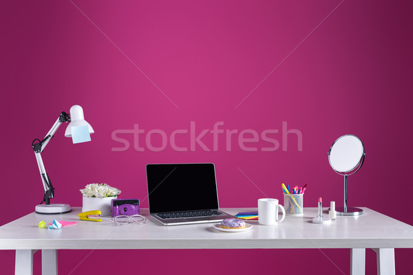 laptop with blank screen, doughnut with coffee, camera, cosmetics and office supplies on pink Stock photo © LightFieldStudios