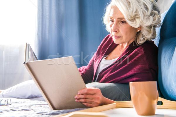 Senior woman reading book       Stock photo © LightFieldStudios