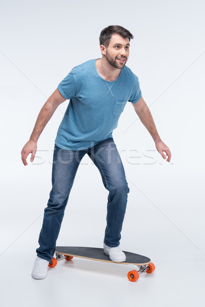 Vista lateral hombre skateboard blanco estudio sonriendo Foto stock © LightFieldStudios