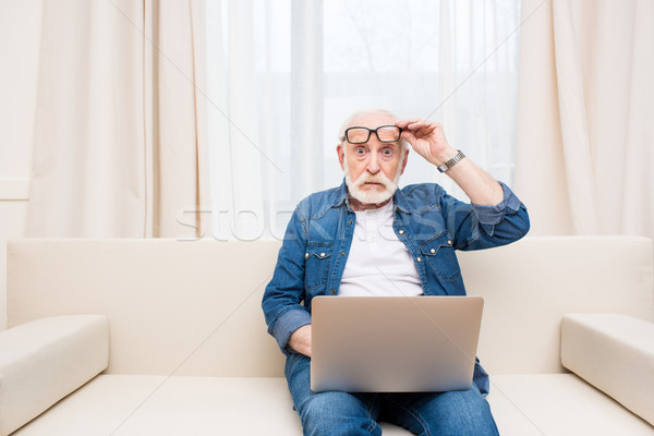 Shocked senior man sitting with laptop on knees and holding eyeglasses Stock photo © LightFieldStudios