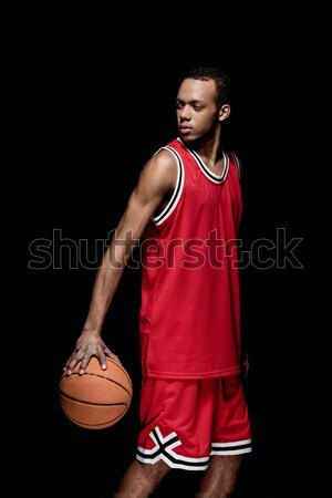Young african american sportsman standing with basketball ball on black Stock photo © LightFieldStudios