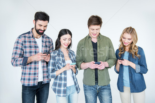 four young friends in casual clothes using smartphones on white Stock photo © LightFieldStudios