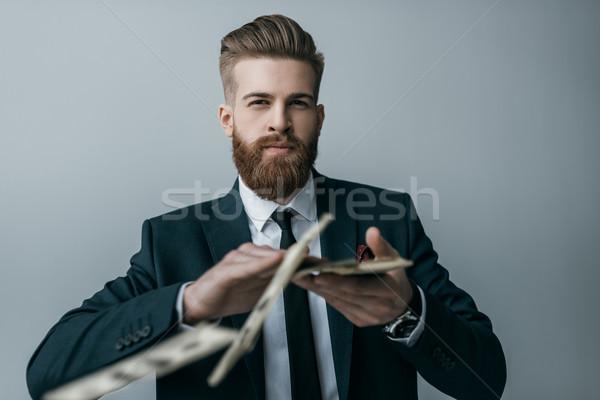 portrait of stylish businessman throwing dollar banknotes on grey Stock photo © LightFieldStudios