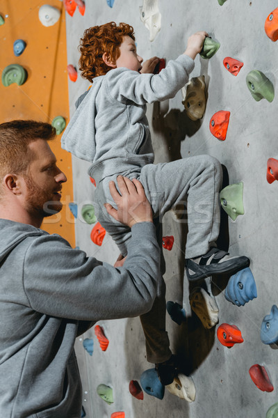 Stock photo: Little boy climbing wall with grips