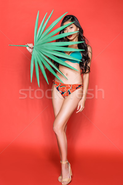 woman covering face with palm leaf Stock photo © LightFieldStudios