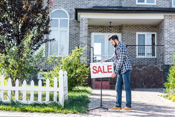 Férfi elad ház fiatalember vásár tábla Stock fotó © LightFieldStudios