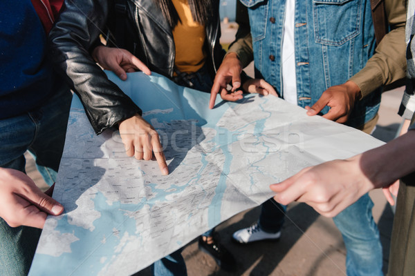 multiethnic friends pointing at map Stock photo © LightFieldStudios