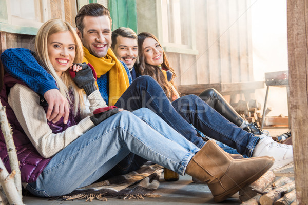 Stock photo: side view of happy friends sitting together and looking to camera