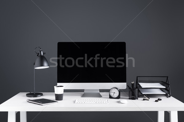 desktop computer with blank screen, clock and office supplies at workplace  Stock photo © LightFieldStudios