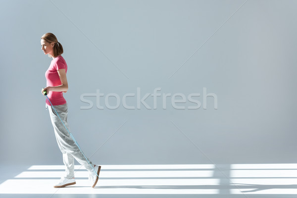 side view of sporty woman standing with skipping rope in hands Stock photo © LightFieldStudios