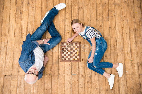 Stock photo: Top view of grandfather and granddaughter playing chess on hardwood floor