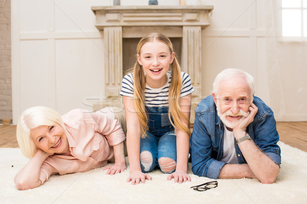 Happy little girl with smiling grandpa and grandma resting together at home Stock photo © LightFieldStudios