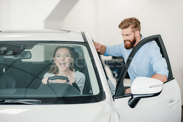 excited young woman sitting in new car and man standing near Stock photo © LightFieldStudios