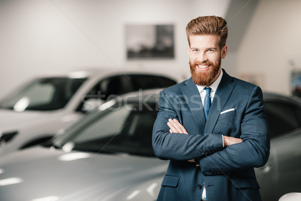 salesman in suit with crossed arms posing and looking at camera in dealership salon   Stock photo © LightFieldStudios