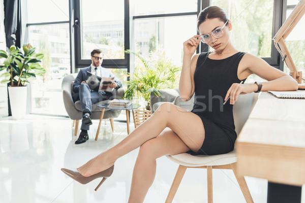 Fiatal ül lábak keresztbe üzletasszony fekete ruha szemüveg Stock fotó © LightFieldStudios