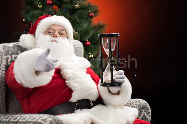 Santa Claus with hourglass  pointing at camera  Stock photo © LightFieldStudios