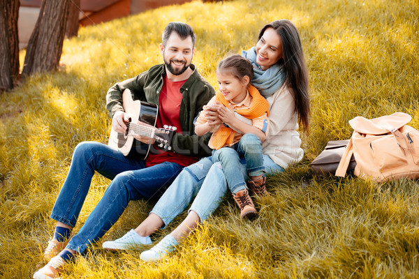 Young man playing guitar with family Stock photo © LightFieldStudios