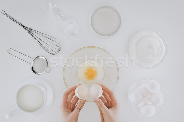 cropped shot of person holding eggshell while cooking pancakes isolated on grey Stock photo © LightFieldStudios