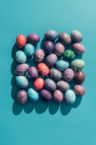 food composition with easter eggs in square shape, on blue Stock photo © LightFieldStudios