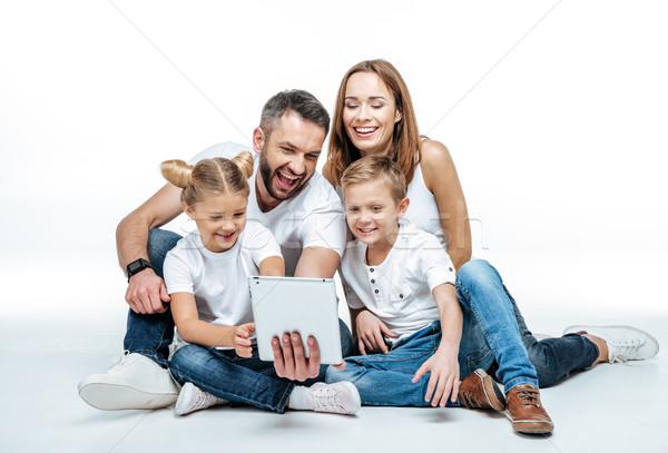Smiling family using digital tablet Stock photo © LightFieldStudios