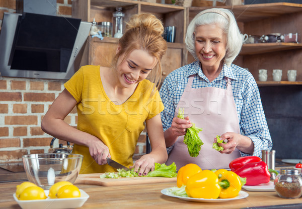 Stock photo: Granddaughter and grandmother cooking together