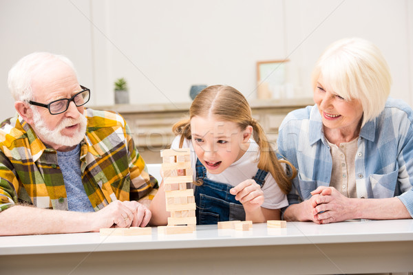 Happy grandparents with granddaughter playing jenga game together at home  Stock photo © LightFieldStudios