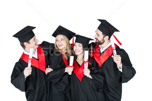 Happy students in academic caps standing embracing with diplomas   Stock photo © LightFieldStudios