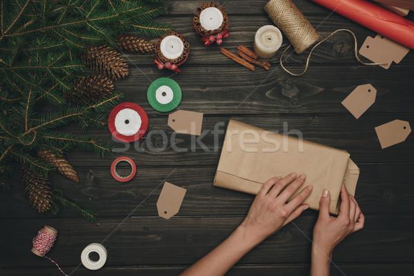 woman wrapping christmas gift Stock photo © LightFieldStudios