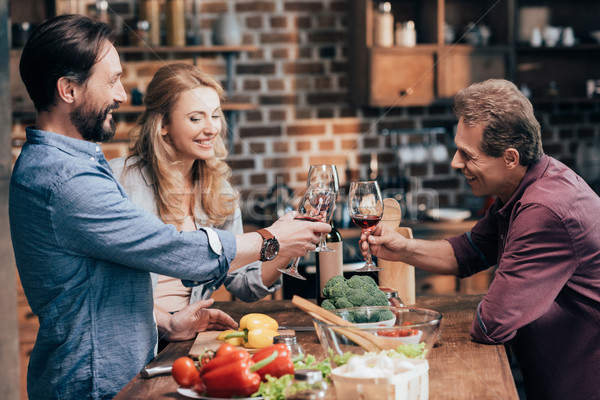 friends drinking wine while cooking dinner Stock photo © LightFieldStudios