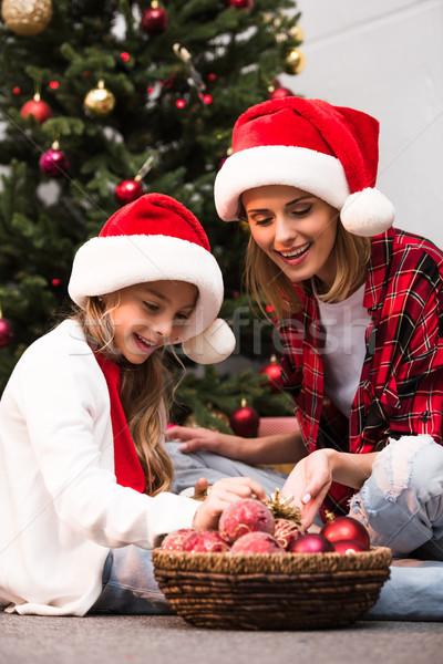 Anya lánygyermek karácsonyfa derűs mikulás sapkák Stock fotó © LightFieldStudios