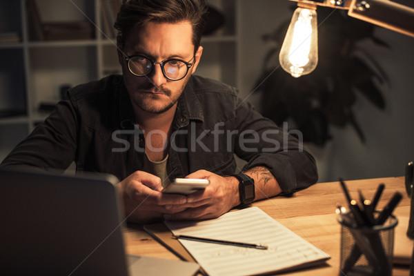 Figyelmes okostelefon fiatal zeneszerző munkahely este Stock fotó © LightFieldStudios