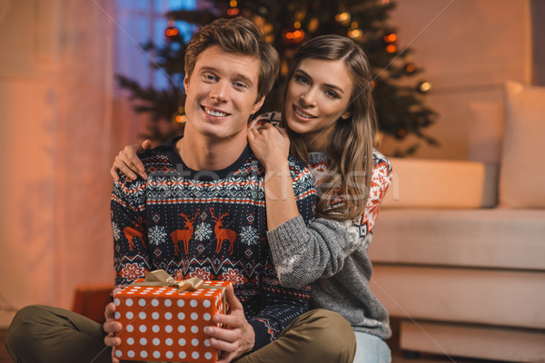 woman hugging boyfriend with christmas gift Stock photo © LightFieldStudios