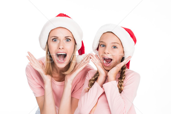 excited mother and daughter in santa hats Stock photo © LightFieldStudios