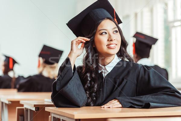 Student dziewczyna ukończeniu kostium asian posiedzenia Zdjęcia stock © LightFieldStudios