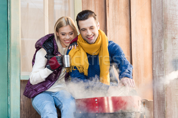 Happy young couple in warm clothes sitting together near grill on porch Stock photo © LightFieldStudios