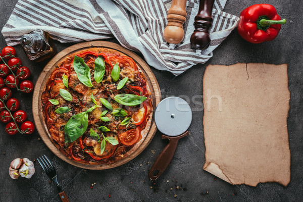 top view of delicious pizza with cutter and blank paper on concrete table Stock photo © LightFieldStudios