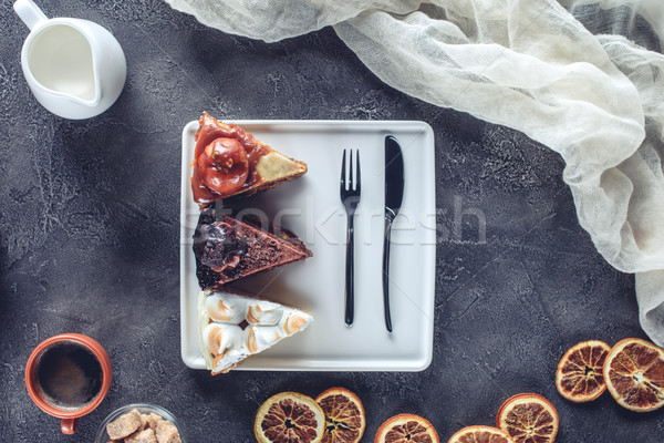 top view of delicious pieces of different cakes on plate Stock photo © LightFieldStudios