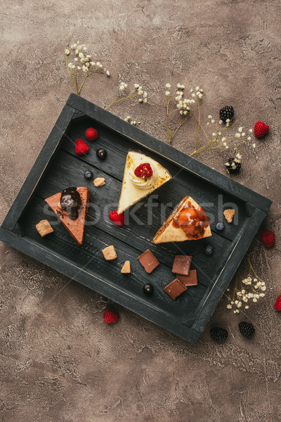 top view of pieces of delicious cakes with chocolate and berries on wooden tray    Stock photo © LightFieldStudios